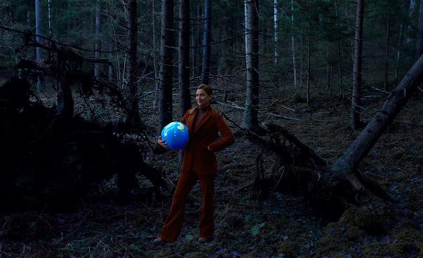 Kvinna i mörk skog med en jordglob under armen.