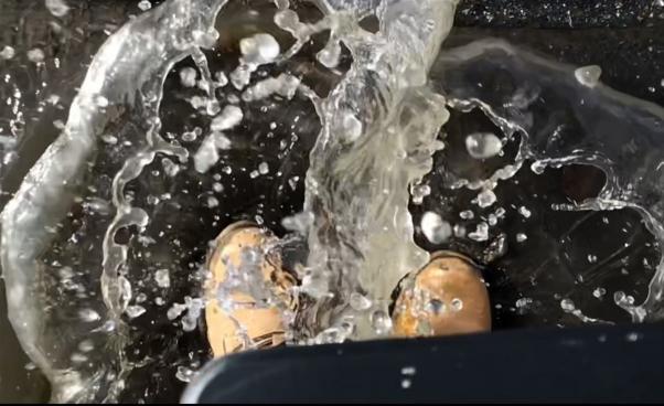 två fötter med skor på står i vatten