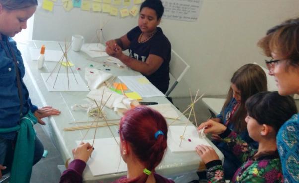 Barn skapar vid bord. Foto