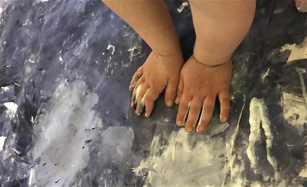 Två barnhänder trycker färg mot textil. (bild)