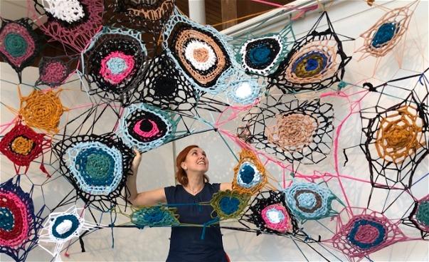 Virkade större verk sammanfogade i rumslig skulptur med kvinna som håller i verket med händerna. (bild)