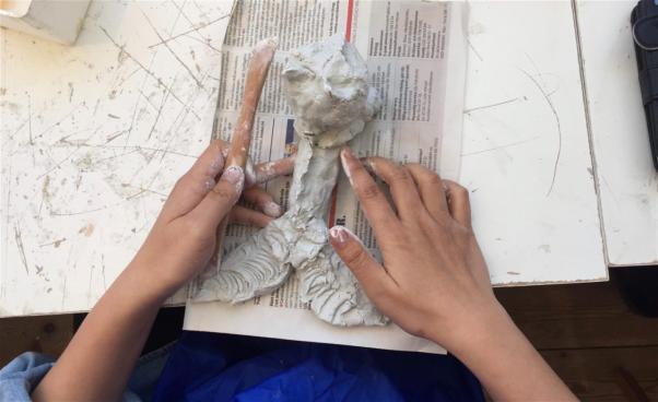 Händer modellerar lerfigur