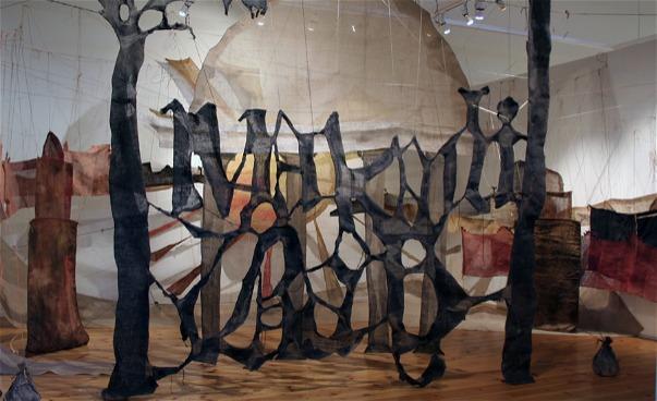Textilt verk med bokstäver och träd i rum. (bild)