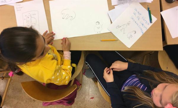 Barn som ritar och pratar. Foto