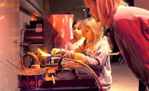 Kvinnlig konstnär med två barn som provar på arbete i glashytta. (bild)