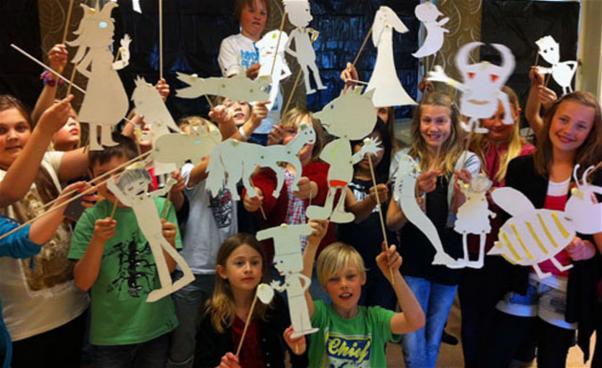 Foto av barn som håller upp sina skuggspelsdockor