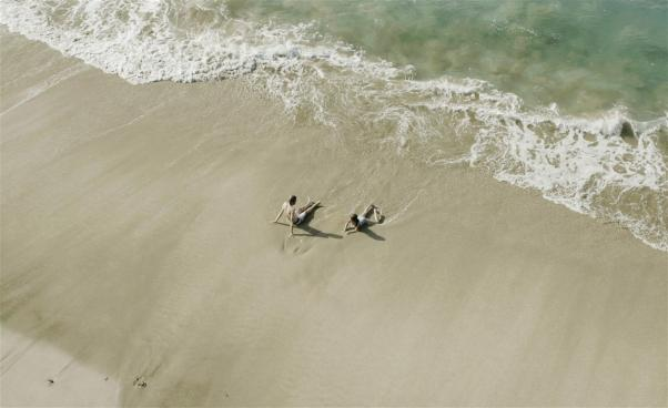 Två ungdomar på en sandstrand