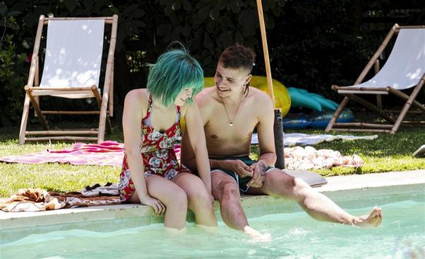 Ungdomar sitter på poolkant