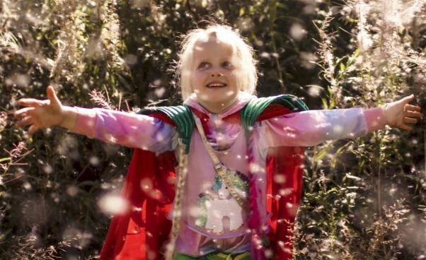 Superhjälteflicka håller ut armarna och ler