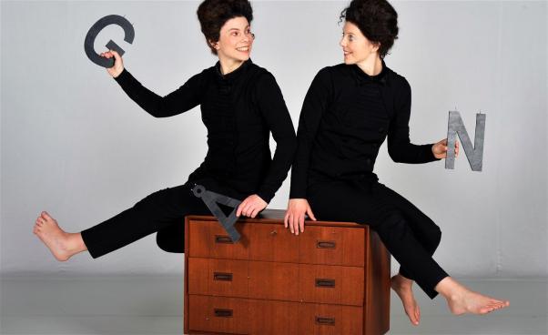 två kvinnor sitter på en byrå och håller i bokstäver